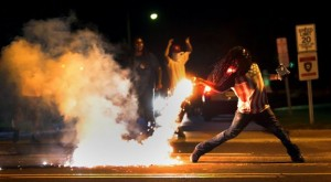 Ferguson-Demonstrator-throws-back-tear-gas-canister